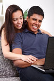 Couple using a laptop and smiling — Stock Photo