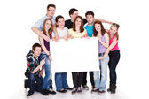 Smiling group of friends with banner — Stock Photo