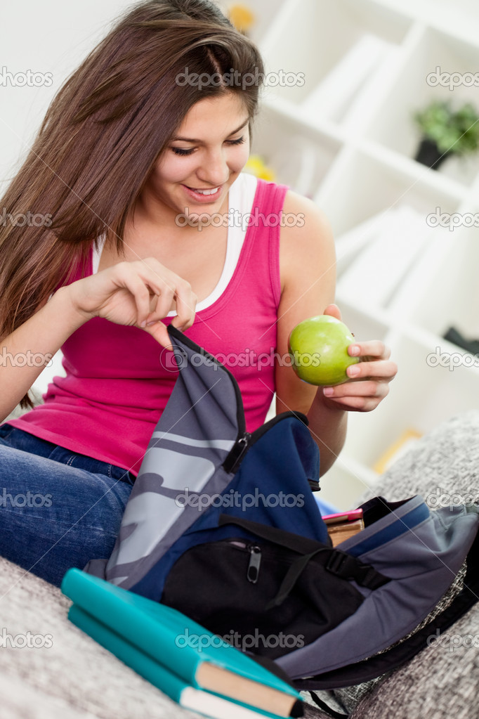 Teen girl  packing book bag preparing for school. — Stock fotografie #10785802