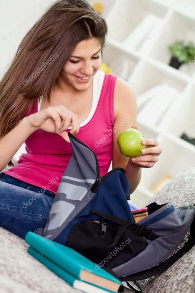 Teen girl  packing book bag preparing for school.  Stockfoto #10785802