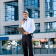 Busy businessman outdoor with documents — Stock Photo