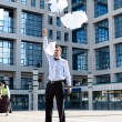 Young businessman throwing away his papers — Stock Photo
