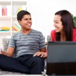 Happy young couple using laptop at home — Stock Photo