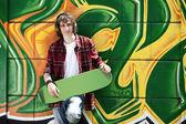 Young man listening music near a graffiti wall — Stock Photo
