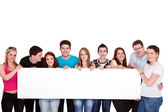 Group of friends standing together with white billboard — Stock Photo