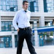 A young businessman is walking and holding a briefcase — Stock Photo