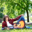 Man in park with acoustic guitar - Stock Photo