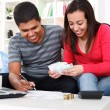 Smiling couple paying bills at home - Stockfoto