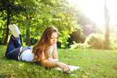 Young woman reading in park — Stock Photo