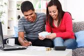 Couple souriant, payer les factures à la maison — Photo