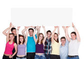 Group of nine young smiling holding blank banner — Stock Photo