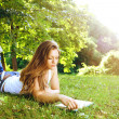 Stock Photo: Young womreading in park