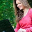 Young woman with laptop in park - Stock Photo
