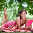 Smiling, young woman reading book while lying on green grass — Stock Photo