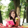 Girl with book and apples — Stock Photo #11473449