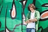 Giovane ragazzo in posa contro un muro di graffiti — Foto Stock