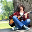 Stock Photo: Man playing guitar in the park