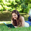 Young woman with headset reading book in park — Stock Photo