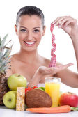 Young woman with fresh fruit and tape measure — Stock Photo