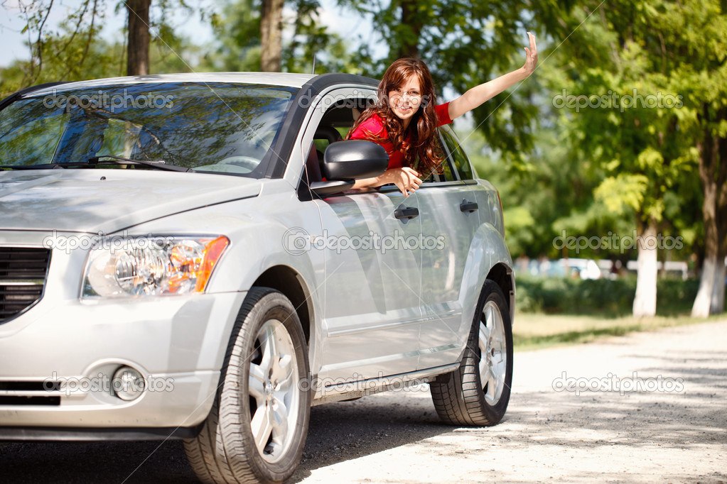Happy woman in car waving out the window — Stock Photo #11926818