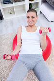 Young woman exercising with dumbbells laying on a fitness ball — Stock Photo