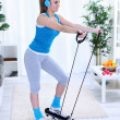 Woman exercising at home on stepper trainer - ストック写真