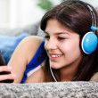 Teenager holds smartphone and listens to music — 图库照片
