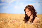 Smiling woman in golden wheat — Stock Photo