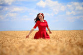 Girl in a red dress walking through wheat field. — Stock Photo