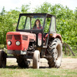 Young girl driving tractor — Stock Photo