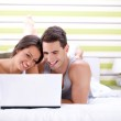 Young couple using laptop while lying on bed — Stock Photo