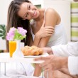 Beautiful young woman in bed with her husband serving breakfast — Stock Photo