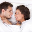 Couple lying in bed smiling — Stock Photo