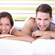 Happy young couple lying on bed — Stock Photo