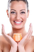 Beautiful smiling young woman with cream — Stock Photo