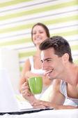 Smiling couple having fun with laptop — Stock Photo