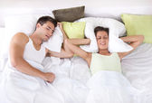 Upset woman in bed with her boyfriend snoring — Stock Photo