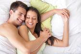 Jeune couple heureux au lit — Photo