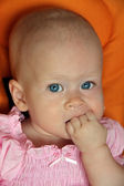 Portrait of cute baby girl sucking fist — Stock Photo