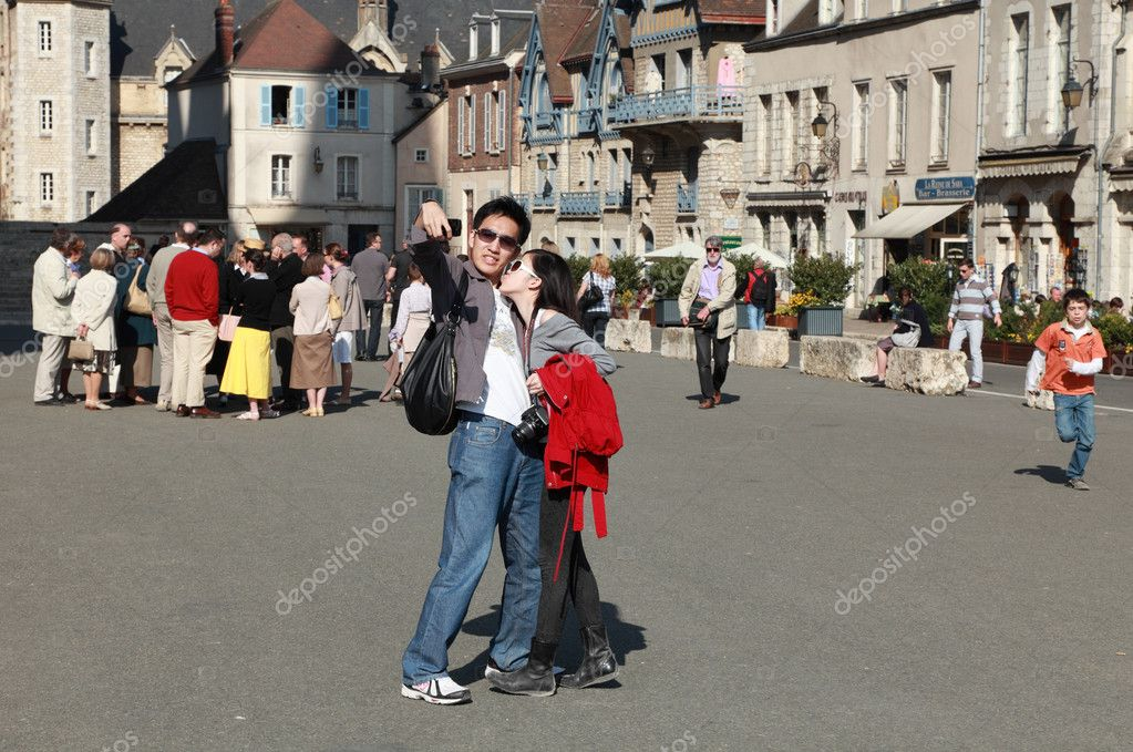 Chartres,France- April 24th, 2010: Image of a couple of Asian tourists photographing themselves using a mobile phone in the downtown of Chartres in a sunny day.Chartres is a small city in northern France.It is best known for the Cathedral of Chartres — Stock Photo #10741322