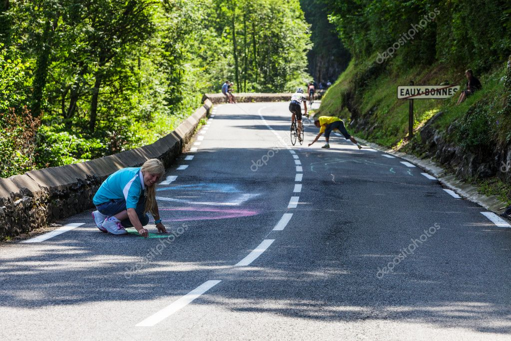 Eaux-Bonnes, France, July 15th 2011:A woman painting on the road to mountain pass Aubisque,in Pyrenees Mountains, before the appearance of the cyclists in the 13th stage of Le Tour de France 2011 — Stock Photo #11871656