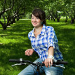 Stock Photo: Young girl on bicycle in garden
