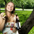 Portrait of laughing girl with wine and pear in the apple orchar — Stock Photo #10818336