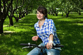 Young girl on a bicycle in the garden — Stock Photo