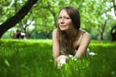 Beautiful woman is lying on the grass — Stock Photo