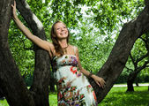 Beautiful girl laughing in the apple orchard — Stock Photo