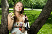 Portrait of laughing girl with wine and pear in the apple orchar — Stock Photo