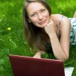 Attractive girl with a laptop in the park — Stock Photo