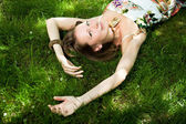 Smiling woman relaxes on the grass — Stock Photo