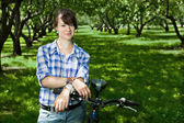 A young girl with a bicycle in the park — Stock Photo